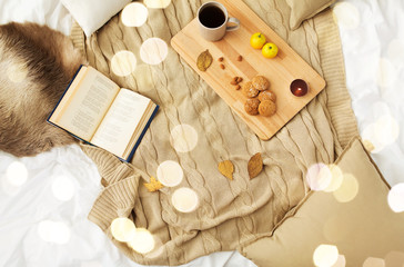 Fototapete - hygge and cozy home concept - cookies, lemon tea, book and leaves in bed