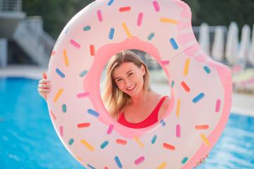 Sexy girl in a red bikini posing near the swimming pool
