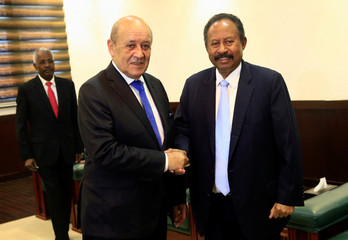 Sudan's prime minister Abdalla Hamdok shakes hands with French Foreign Minister Jean-Yves Le Drian during their meeting in Khartoum