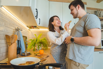 couple at the kitchen. woman feeding man. cooking together
