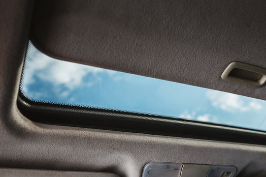 Blue sky through an open car sunroof - view from the passenger compartment