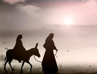 Christmas religious nativity concept: Silhouette pregnant Mary and Joseph with a donkey on star of cross background
