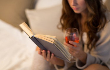 Fototapete - christmas, leisure and comfort concept - close up of young woman reading book and drinking rose wine from glass at home