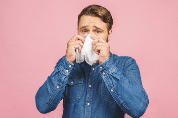 Studio picture with a young man with handkerchief. Sick guy isolated has runny nose. man makes a cure for the common cold