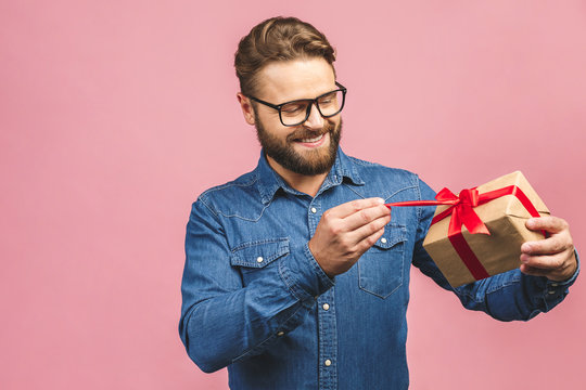 Happy holiday, my congredulations! Portrait of an attractive casual man giving present box and looking at camera isolated over pink background.