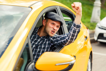 Photo of angry driver in plaid shirt sitting in yellow taxi on summer.