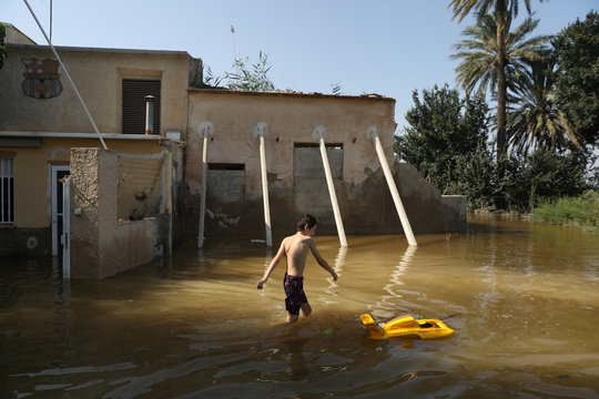 The youngest child in the Canizares family plays in the flooded vegetable garden of their summer home after torrential rains in Dolores near Alicante