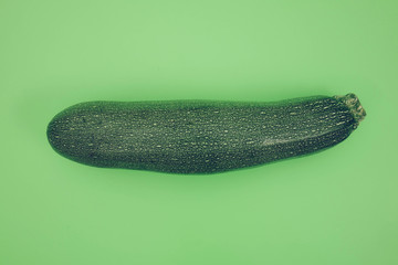 Zucchini on vibrant green background.