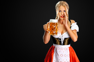 Sexy oktoberfest girl waitress, wearing a traditional Bavarian or german dirndl, serving big beer mug with drink isolated on black background. Woman have a secret.