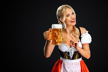 Smiling young sexy oktoberfest girl waitress, wearing a traditional Bavarian or german dirndl, serving big beer mug with drink isolated on black background.