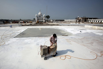 A laborer operates a machine to polish a newly installed marble flooring at the site of the Gurdwara Darbar Sahib, which will be open this year for Indian Sikh pilgrims, in Kartarpur
