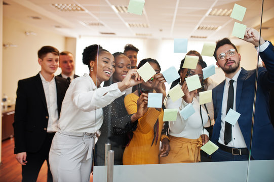 Team of multicultural young people pointing on glass with colorful paper notes. Diverse group of male and female employees in formal wear using stickers.