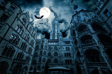 Marienplatz at night, Munich, Germany. Creepy mystery view of dark Gothic Town Hall with bats. Old spooky castle or palace in full moon. Scary gloomy scene with horror and terror for Halloween theme.