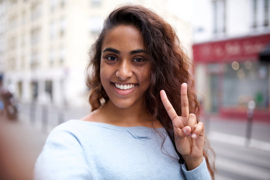 happy Indian woman taking selfie with peace hand sign