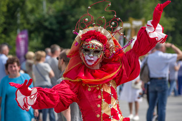 Actors in colorful costumes and Venetian masks at the festival of the city.