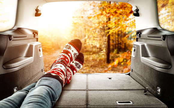 Woman legs in car interior and autumn landscape of forest