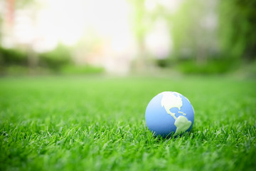 Global Warming, Environment and Ecology Concept. Close up of mini world ball on green grass lawn with rain drop. Wall mural