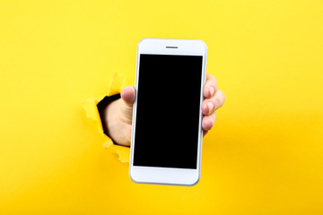 Hand holding smartphone from yellow torn paper