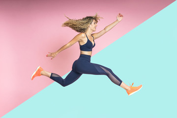 beautiful blond-haired woman with fitness lifestyle wearing sportswear is running and jumping with her hair in motion on an isolated background of various colors