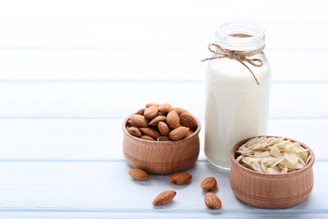 Wall Mural - Almond and milk in bottle on wooden table