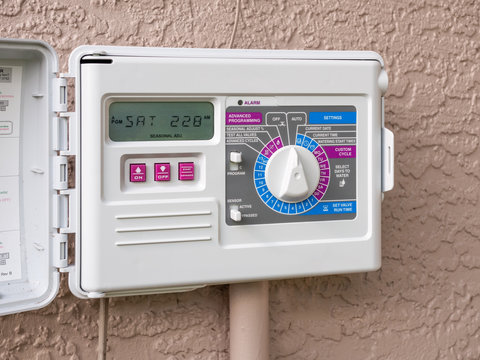 Automatic electric outdoor irrigation timer. Closeup of programmable lawn watering system.