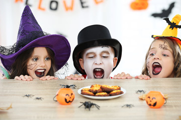 Young two girls and boy in halloween costumes looking on the cookies Wall mural