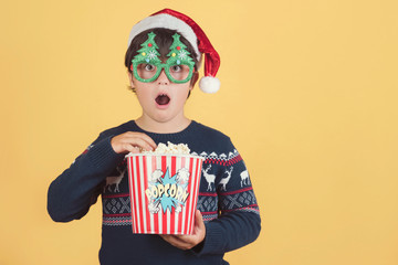 Surprised child Wearing Christmas Hat with popcorn