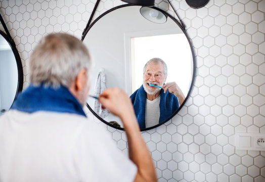 A senior man brushing teeth in bathroom indoors at home. Copy space.