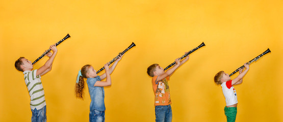Four people, a musician, stand in a row and play clarinets, photos of children on a yellow background. Wall mural