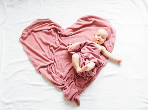 Smiling baby lying on a pink blanket in the shape of a heart