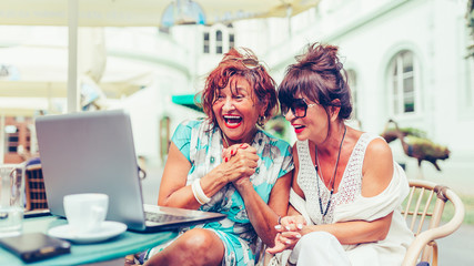 Two excited senior women reading good news online on laptop