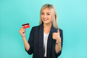 beautiful young woman in a black suit on a blue background with a credit card in her hands