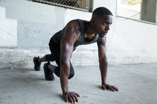 African american male athlete preparing for a jog, stretching, fitness and exercise in urban theme