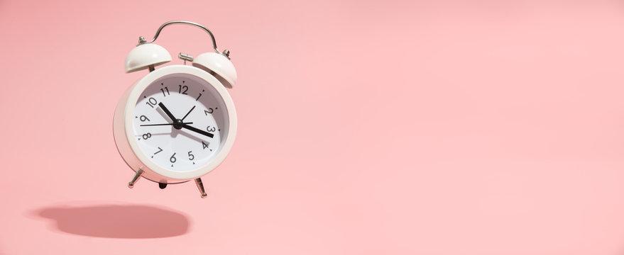 Pink Alarm clock on pastel pink background.