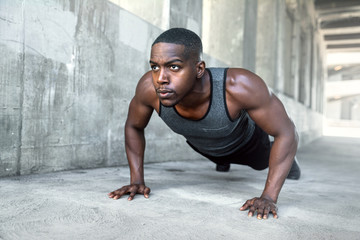 Black male working out alone outside on concrete, pushups in urban downtown city exercise