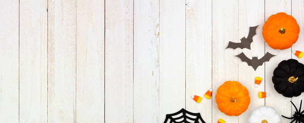 Halloween corner border banner with black, orange and white decor and candy over a white wood background. Top view with copy space.