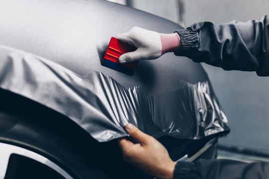 Car wrapping specialist putting vinyl foil or film on car. Selective focus.