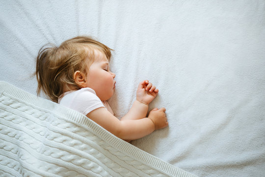 Cute little baby sleeping peacefully on bed at home covered with blanket. Child daytime sleeping schedule