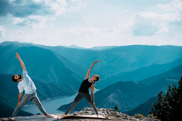Two people is practicing yoga in high mountains