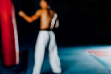 Blurred view of muscular man kick boxing with red punching bag at gym. Blurred image