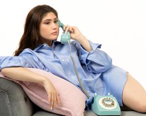 Beautiful Hispanic teen girl talking on vintage phone