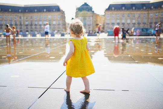 toddler girl having fun famous outdoor water fountain (Miroir d'eau) in Bordeaux