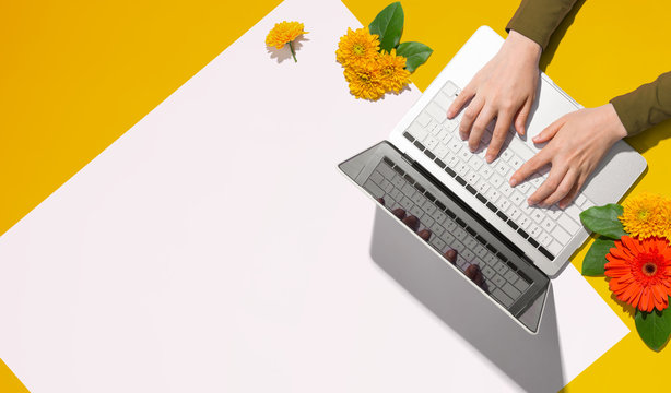 Person using a laptop computer with autumn flowers - overhead view