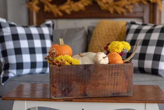 Vintage wooden crate filled with pumpkins and flowers