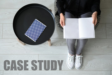 Young woman reading book at home, top view. Concept of study
