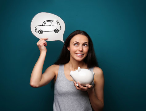 Woman with piggy bank dreaming about new car on color background