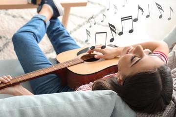 Beautiful woman playing guitar at home