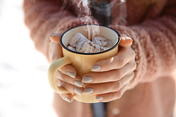 Woman with cup of hot cacao and marshmallows outdoors, closeup