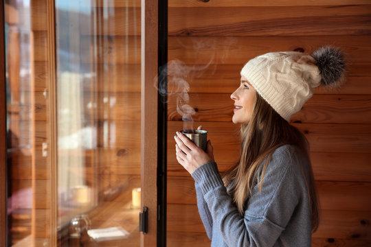 Woman drinking hot mulled wine near window in morning