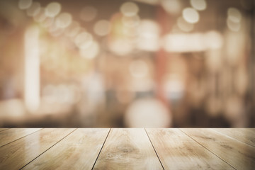 Empty wooden table top with lights bokeh on blur restaurant background, 3D Rendering